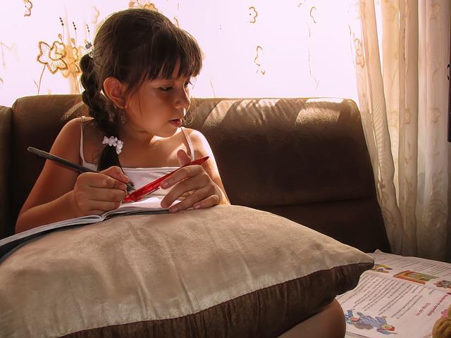 dívka učící se na pohovce
