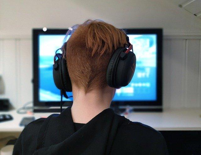 kluk se sluchátky u pc hry